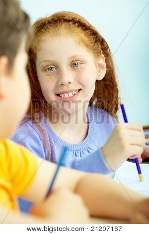 Portrait of smart schoolgirl looking at classmate at drawing lesson
