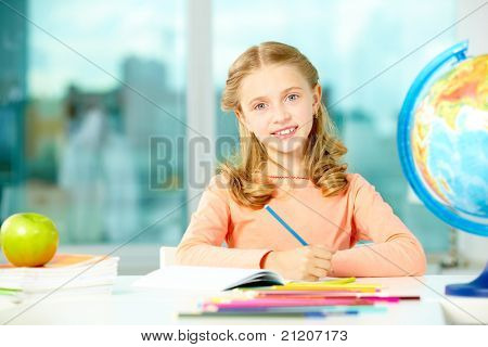Portrait of cute schoolgirl with blue pencil looking at camera in classroom