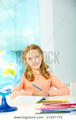 Portrait of smart schoolgirl with blue pencil looking at camera in classroom