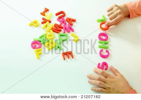Close-up of girl hand making word ?school? from colorful letters