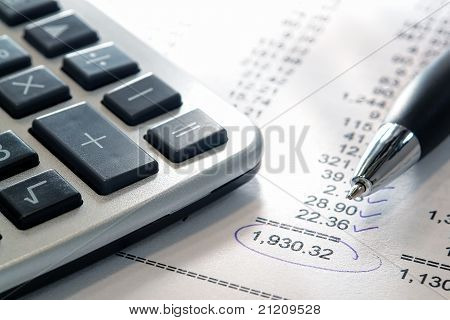 Calculator And Pen On Budget Statement With Checked Numbers