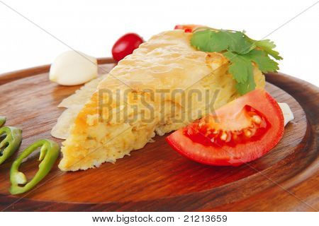 dairy food : cheese casserole piece on wooden plate tomatoes , chives , and garlic isolated over white background