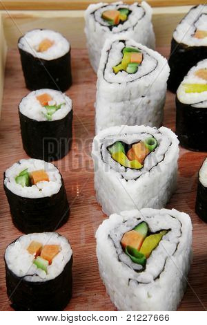 Maki Sushi and Nigiri - Maki Rolls and California rolls made of fresh raw Salmon, Tuna and Eel with Cream Cheese and Avocado . Isolated over white background . on wooden plate