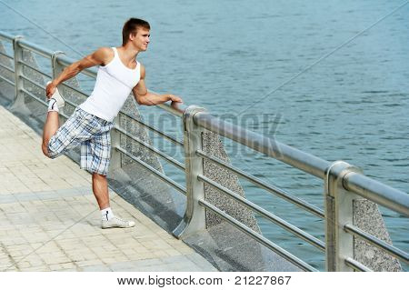 Young athlete man doing stretching warming up before jogging outdoors