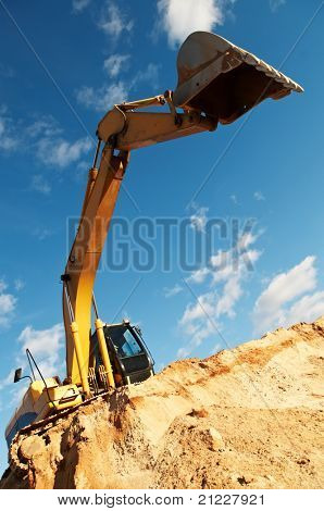 excavator loader machine with risen boom construction site