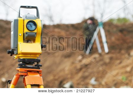 Surveyor equipment theodolite on tripod at building area in front of working surveyor