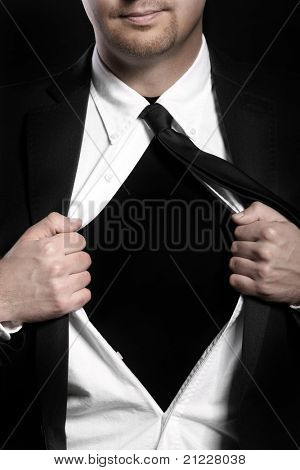 A picture of a young handsome man tearing off his shirt over black background