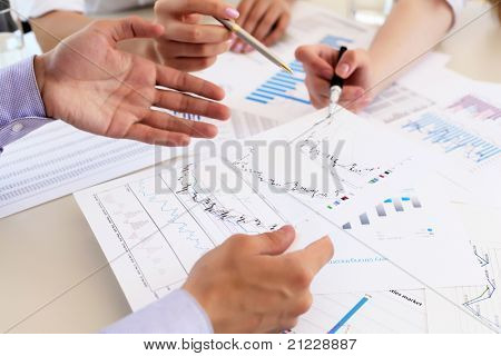 financial and business documents on the table and human hands
