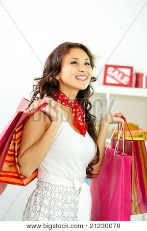 Retrato de morena feliz com paperbags no shopping