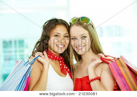 Retrato de clientes felizes com paperbags olhando para câmera