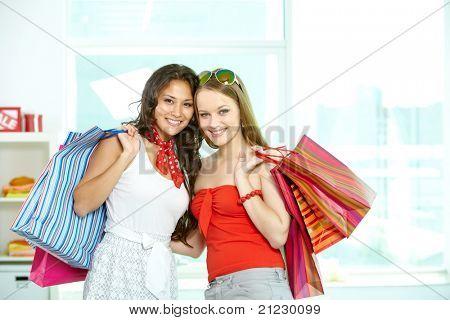 Retrato de meninas felizes com paperbags olhando para câmera