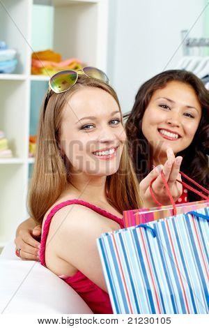 Retrato de compradores felizes olhando para câmera com sorrisos depois das compras