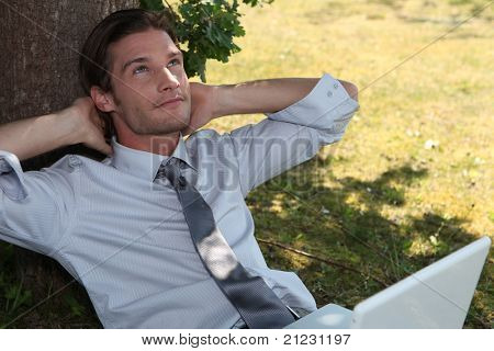 Young exec using a laptop under a tree