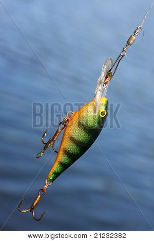 Fishing lure against water level. Close up with shallow DOF.