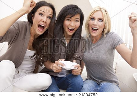 Three beautiful interracial young women friends at home having fun playing video games together and laughing