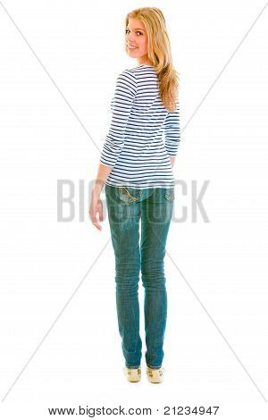 Full length portrait of smiling beautiful teen girl looking back over her shoulder isolated on white