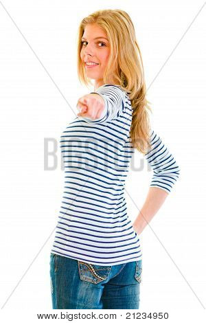 Smiling beautiful teen girl looking back and pointing finger at you isolated on white