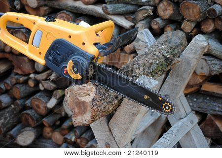 electric chain saw cuts the trunk on stand