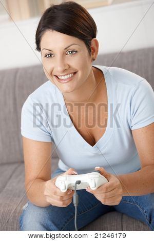 Happy young woman playing video game with controller, smiling.?