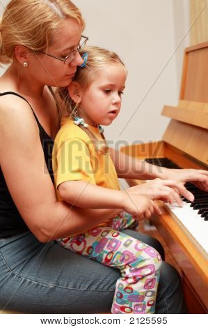 Mother And Daughter Play Piano