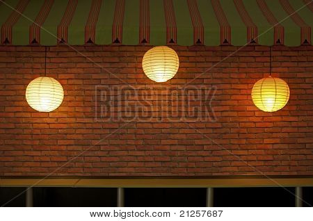 Brick wall with three illuminated lamps