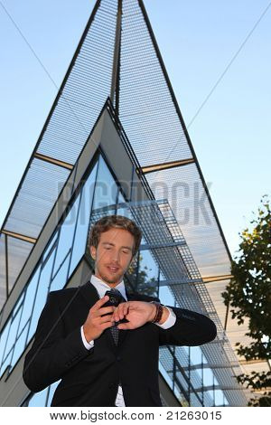 Young businessman checking his phone and watch outside a modern building
