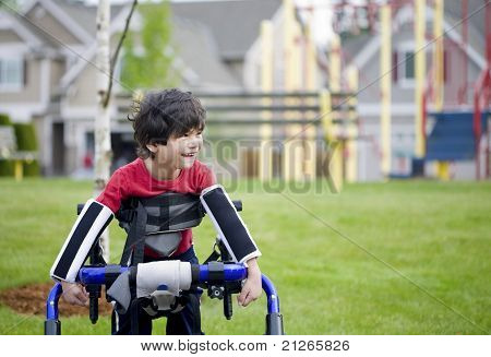 Disabled Four Year Old Boy Standing In Walker Near A Playground
