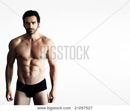 Portrait of a sexy male fitness model in underwear against neutral background with lots of copy space