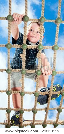 Young boy climbing rope obstacle