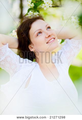portrait of beautiful pregnant woman in the flowering park