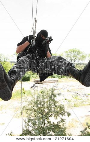 Soldier In Black Mask Hanging On Rope With Ak-47 Rifle