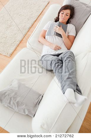Young Cute Female Having A Rest And Reading A Book While Lying On A Sofa