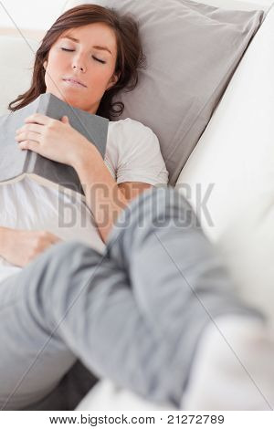 Young Attractive Female Having A Rest And Reading A Book While Lying On A Sofa