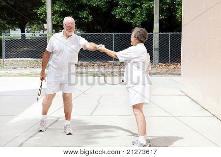 Senior man handing the racquetball to his wife during a friendly game.