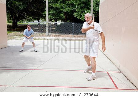 Fit senior man plays raquetball with his adult son.
