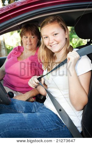 Pretty teen driver fastening her seatbelt.  Mom is about to give her a driving lesson.