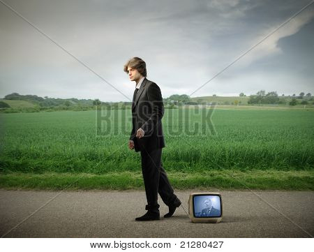 Young businessman walking on a countryside road and carrying a television