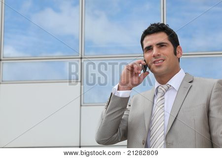 Man using a cellphone outside a mirrored building