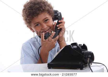 little boy calling with an old telephone