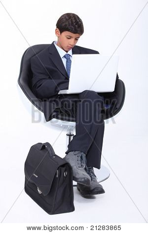 Boy dressed in an adult business suit using a laptop computer