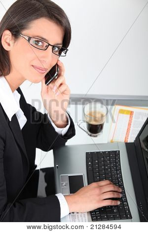 Woman at laptop with coffee and cellphone