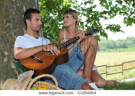 Young couple with picnic basket sat by tree