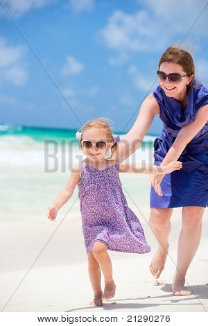 Mother and her little daughter running at tropical beach