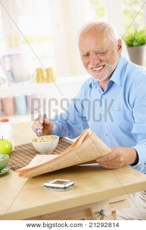 Smiling senior man sitting in kitchen reading papers while having cereal for breakfast.?