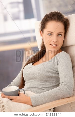 Portrait of attractive young girl, sitting in armchair, relaxing, drinking tea, smiling.?