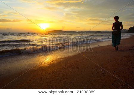 Young woman walking on sandy coastline and looking to a sunset over sea