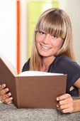 Young woman with blunt fringe reading a book
