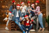 Party with group friends wearing Santas hats. Young people, hipsters sharing good and positive mood poster