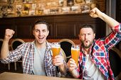 Cheerful Young Handsome Male Friends Having Fun At The Beer Pub Celebrating Victory Of Their Favorit poster