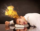 A depressed businessman banging his head in a keyboard and shouting with his head on fire, reflectin poster